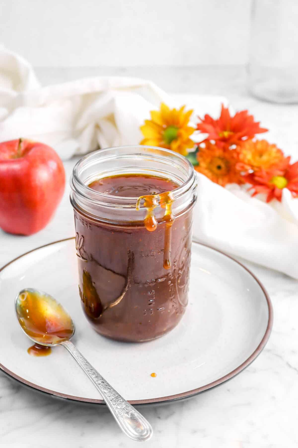 boiled cider in a jar with flowers and an apple behind