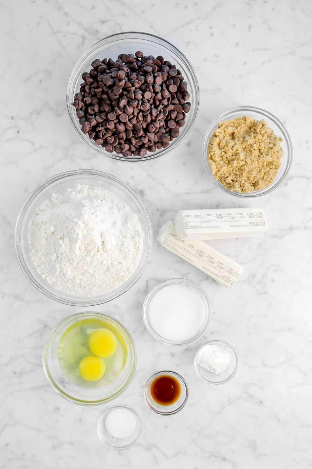 chocolate chips, brown sugar, flour, butter, sugar, eggs, baking powder, vanilla, and salt on a marble counter