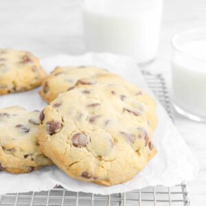 five cookies on a wire cooling rack with two glasses of milk