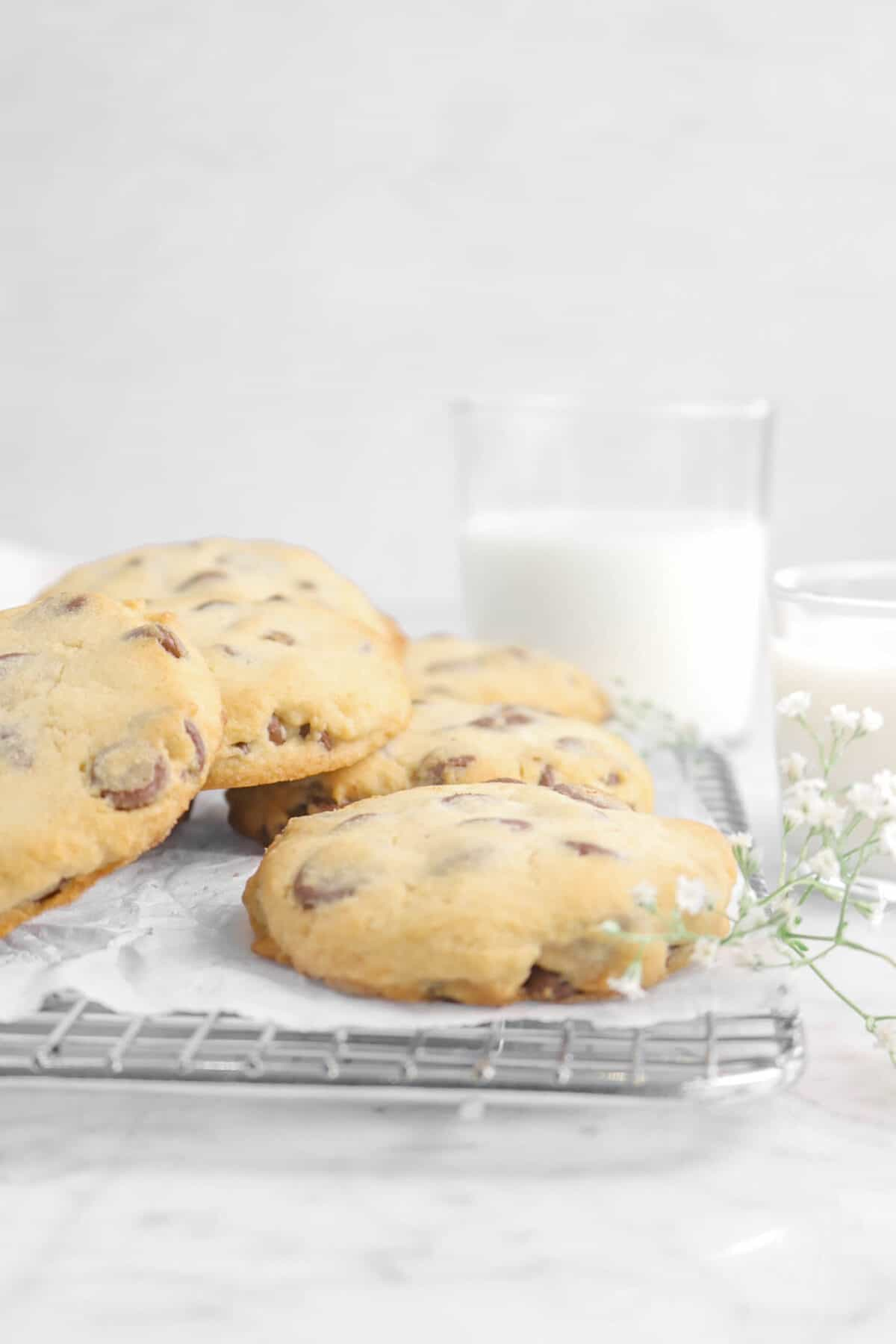 cookies on a wire cooling rack with milk and flowers