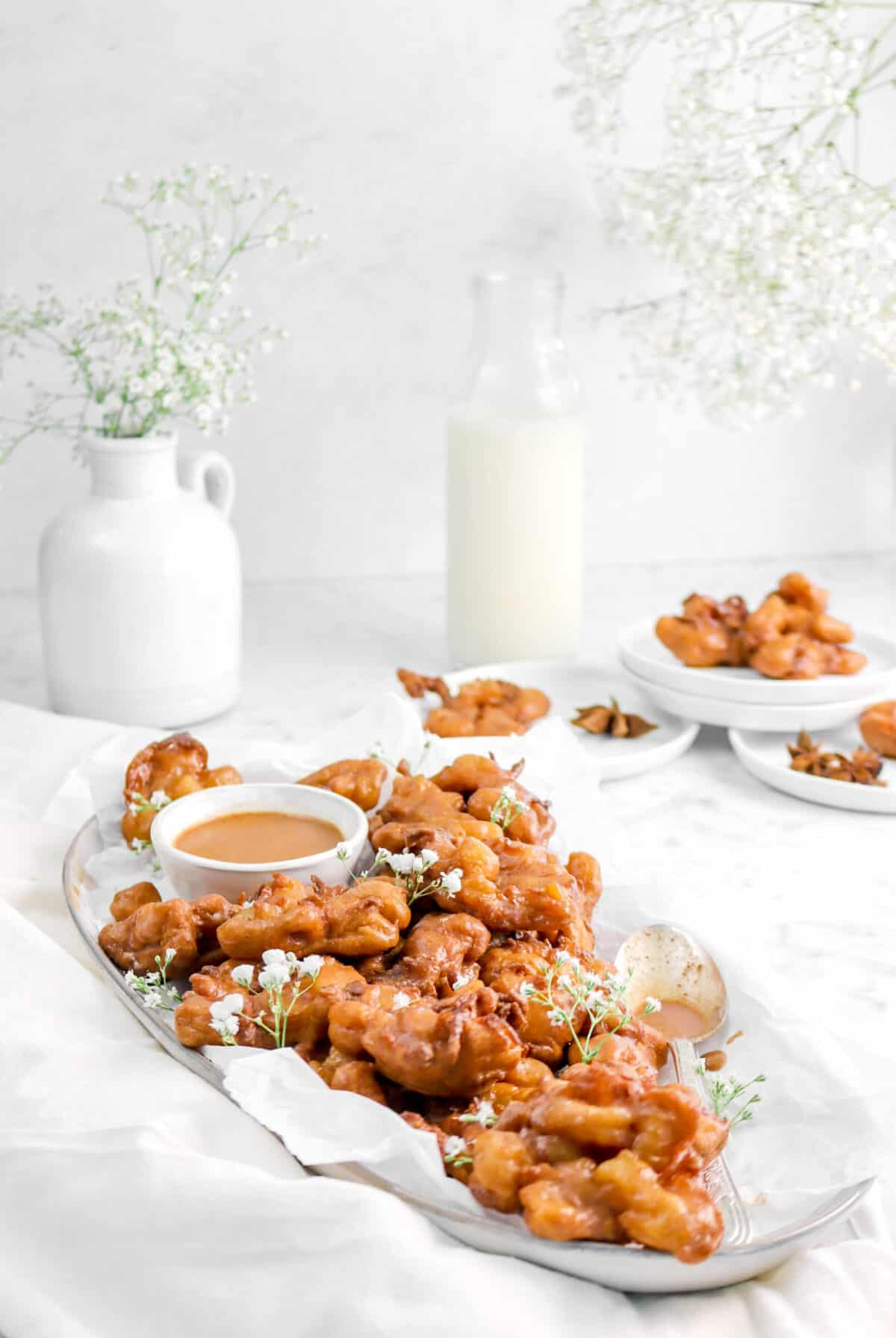 plate of apple pie fritters, with flowers, a spoon, and a glass of milk