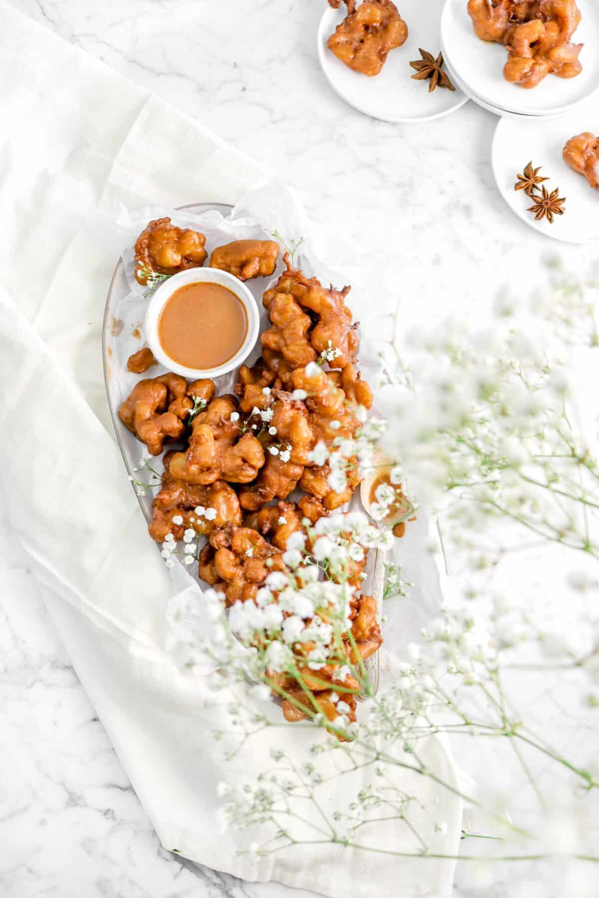 apple pie fritters on a plate with flowers over it, a napkin, and three plates