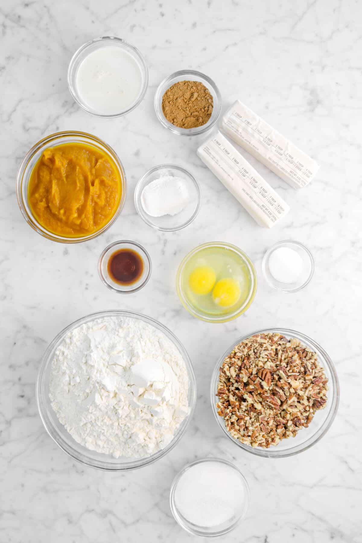 cream, spices, butter, pumpkin, baking powder, vanilla, eggs, salt, flour, pecans, and sugar on marble counter