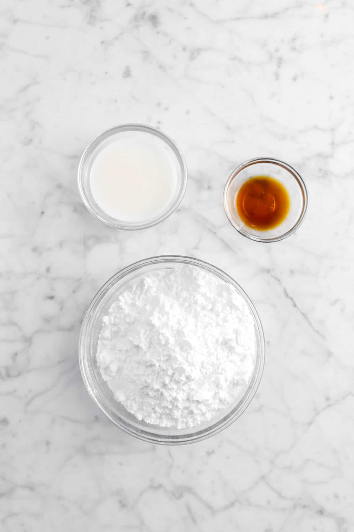 powdered sugar, vanilla, and milk on marble counter