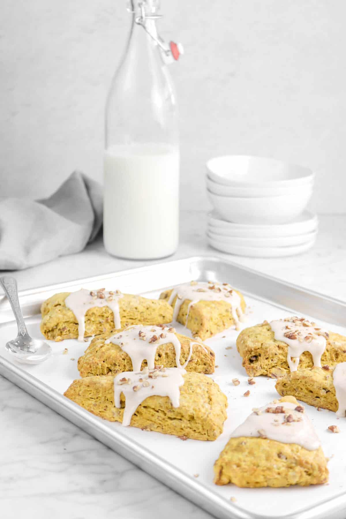 scones on a sheet pan with milk jug, bowls, and plates behind