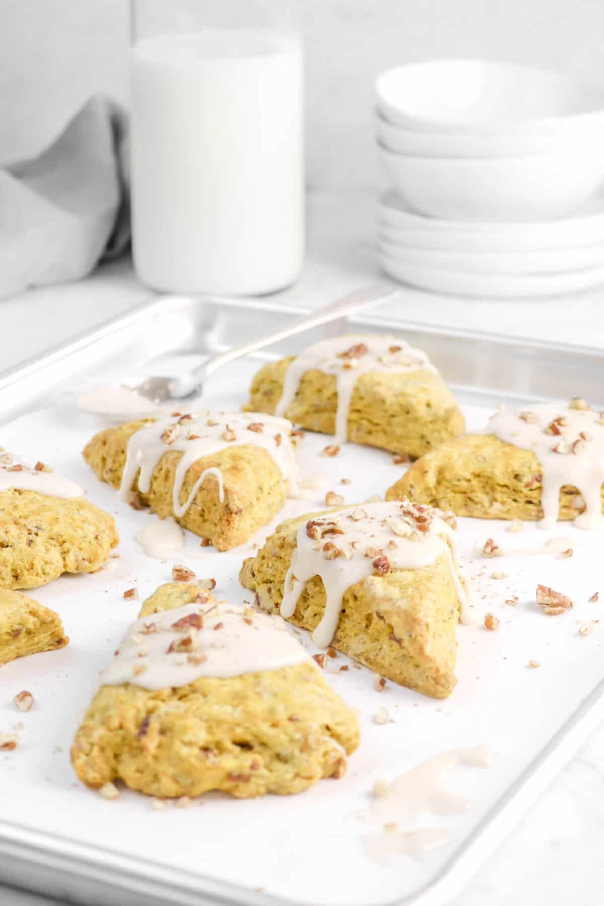 glazed scones on a sheet pan with milk, plates, bowls, and a napkin