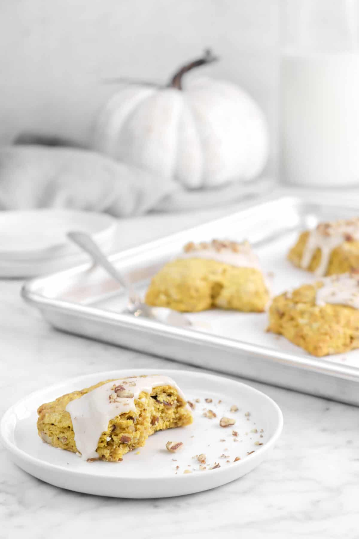 scone on a plate with more scones, a pumpkin, and napkin behind