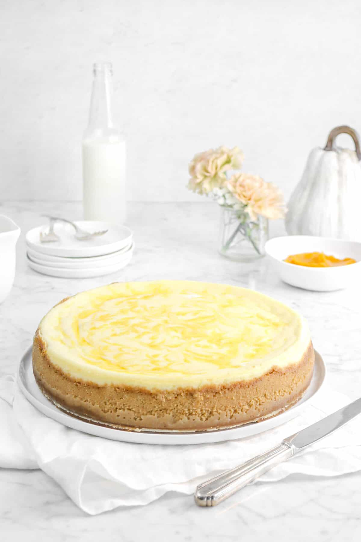 cheesecake on a white plate and napkin with flowers, pumpkin, and plates behind