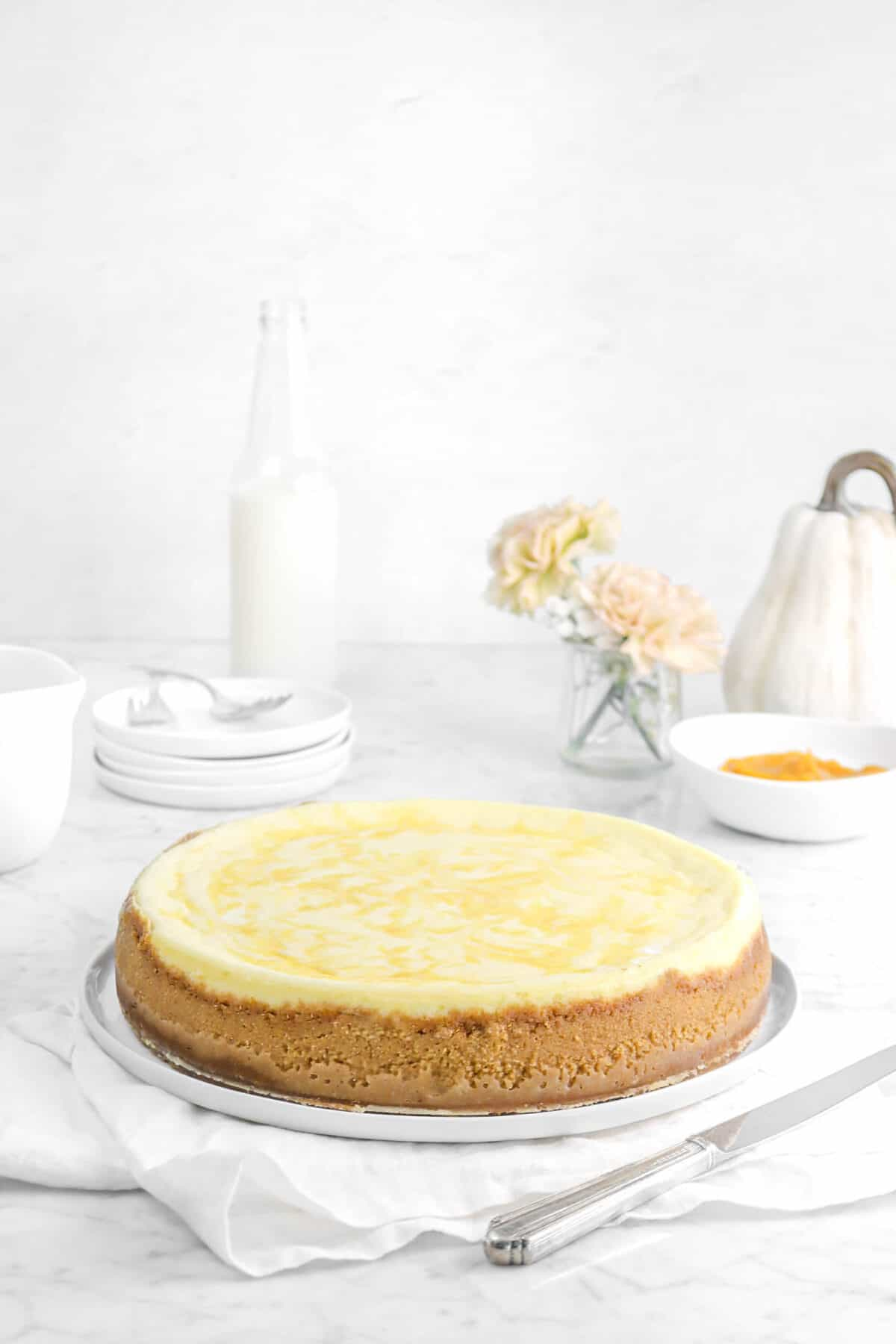 cheesecake on a plate with a knife, napkin, flowers, plates, milk, and white pumpkin behind