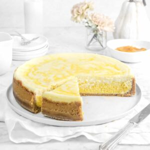 cheesecake on white plate with a slice next to it, flowers, pumpkin, milk glass, and plates behind
