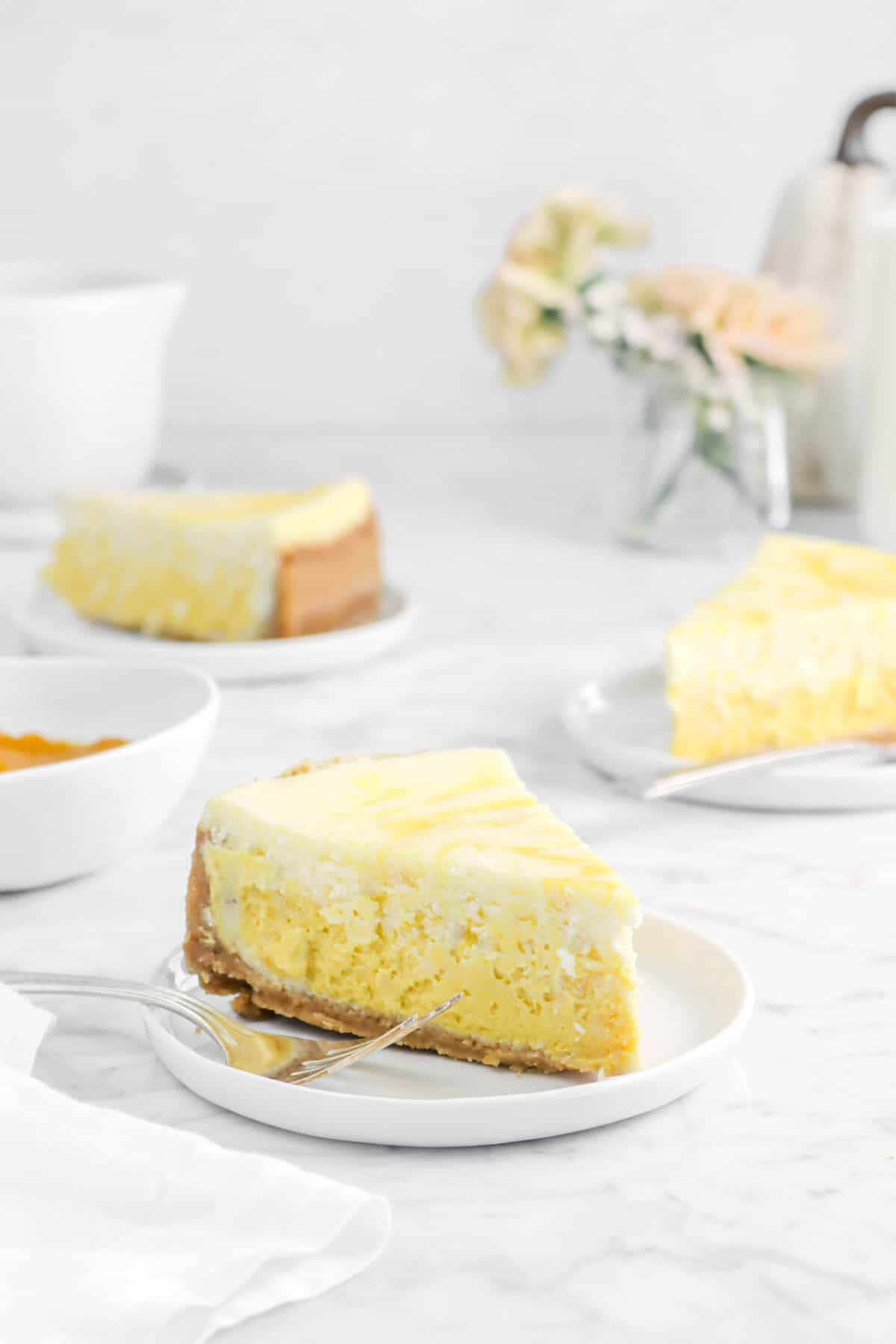three slices of cheesecake on plates with flowers and white pumpkin behind