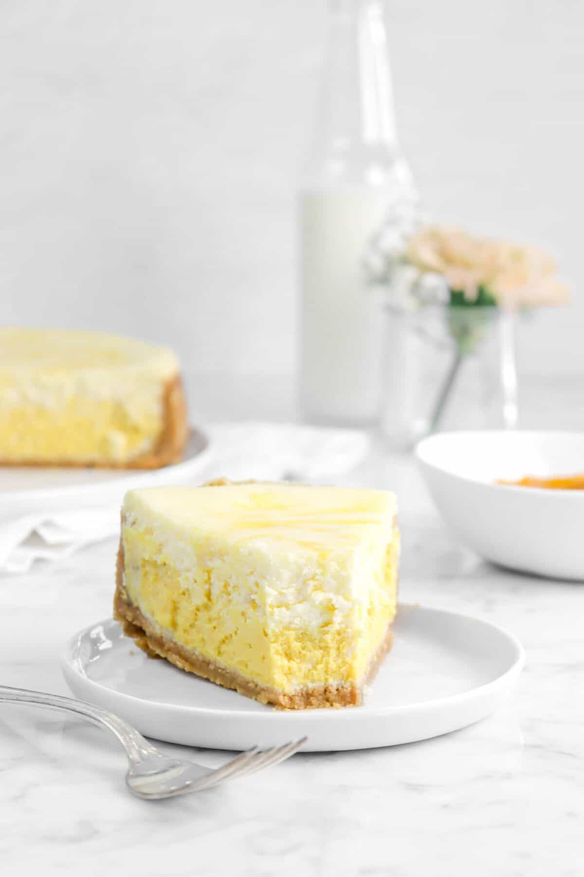 cheesecake slice on a white plate with flowers and milk glass behind