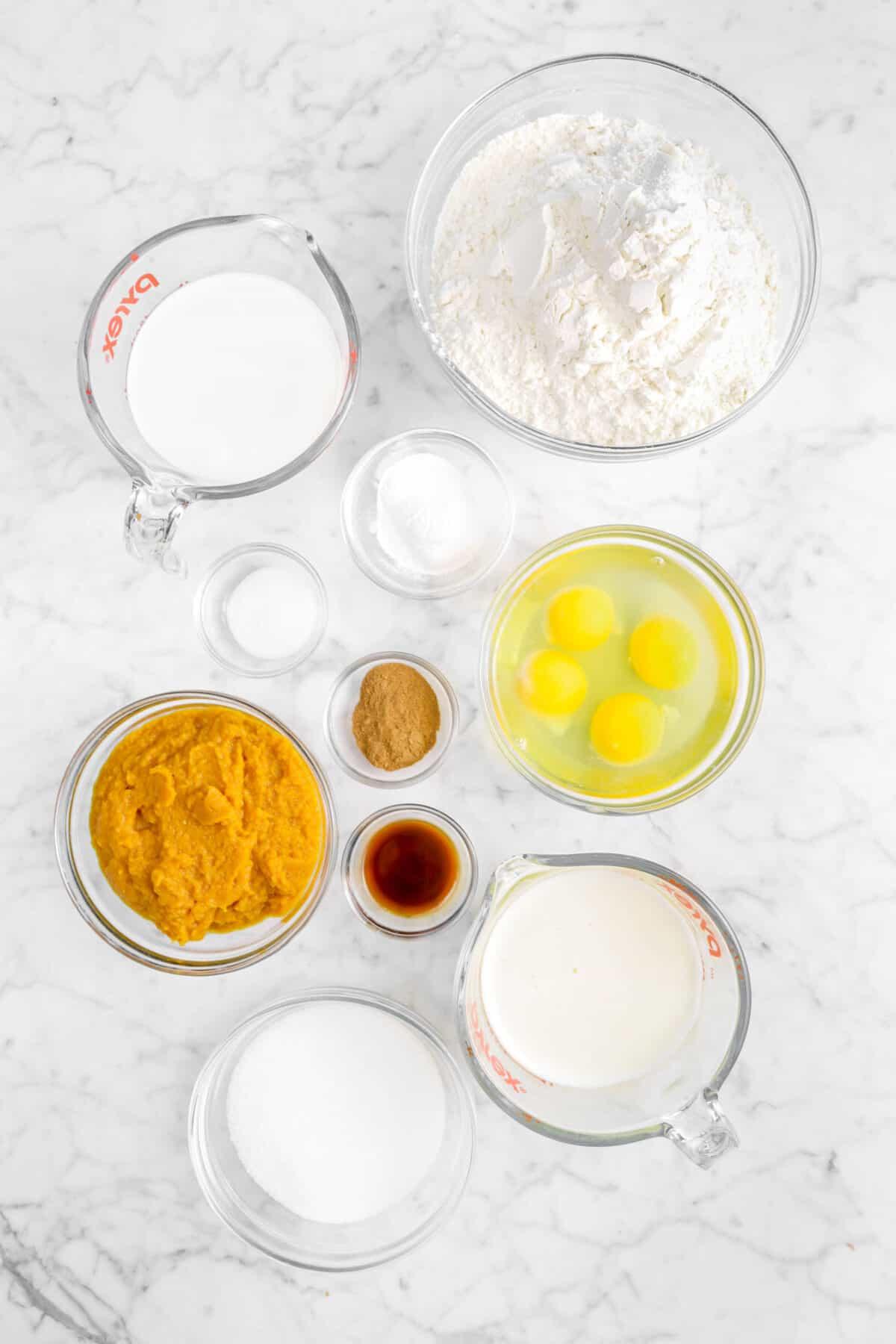 flour, milk, baking powder, salt, spice, eggs, vanilla, pumpkin, sugar, and melted butter on marble counter