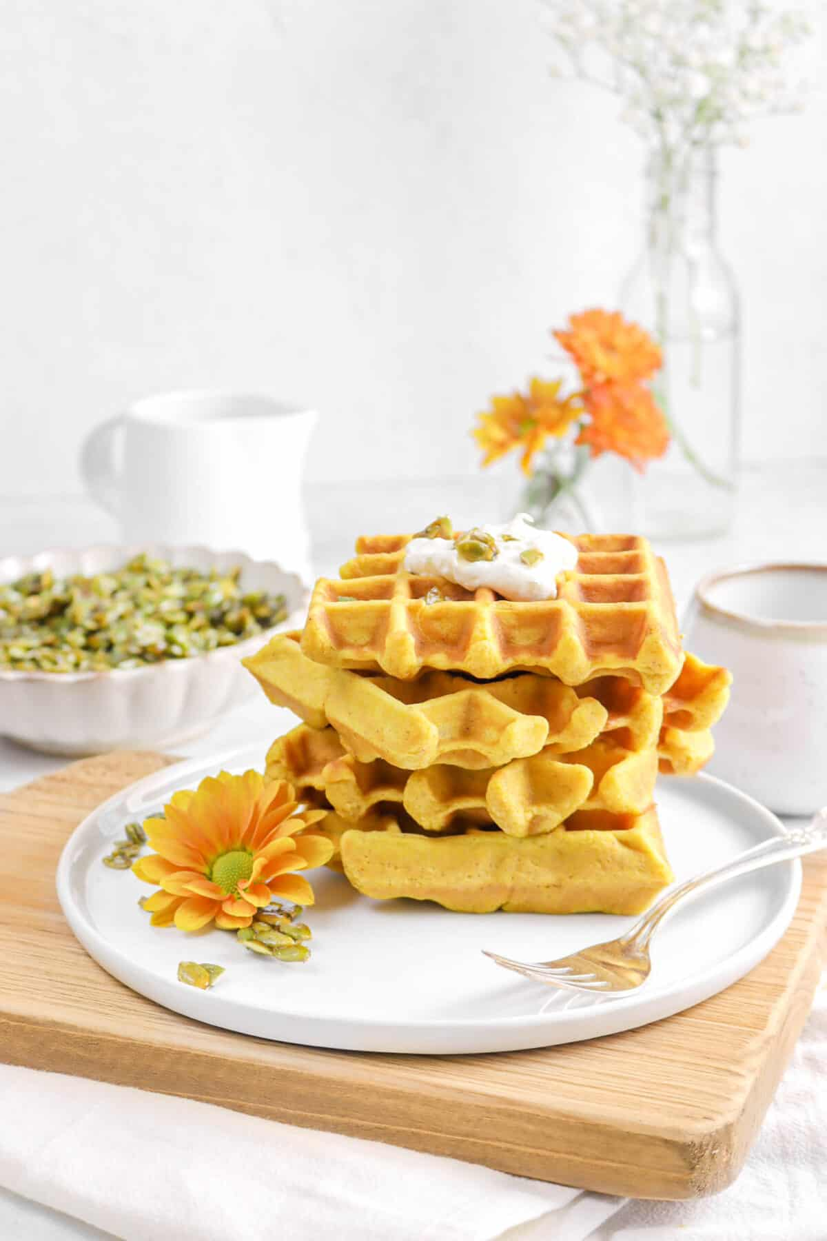 four pumpkin waffles stacked on a white plate with flowers, and candied pepitas