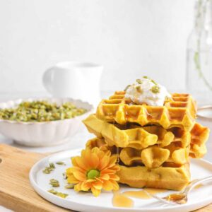 waffles stacked with maple syrup dripping, candied pepitas, with whipped cream on top, and flowers