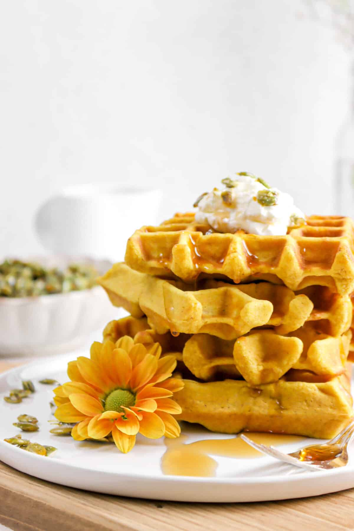 four stacked waffles with whipped cream on top, maple syrup, candied pumpkin seeds, and flowers
