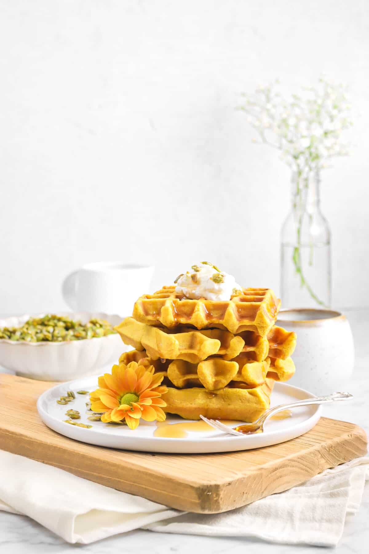 pumpkin waffles stacked on a white plate, on a wood serving board, with candied pepitas, and flowers