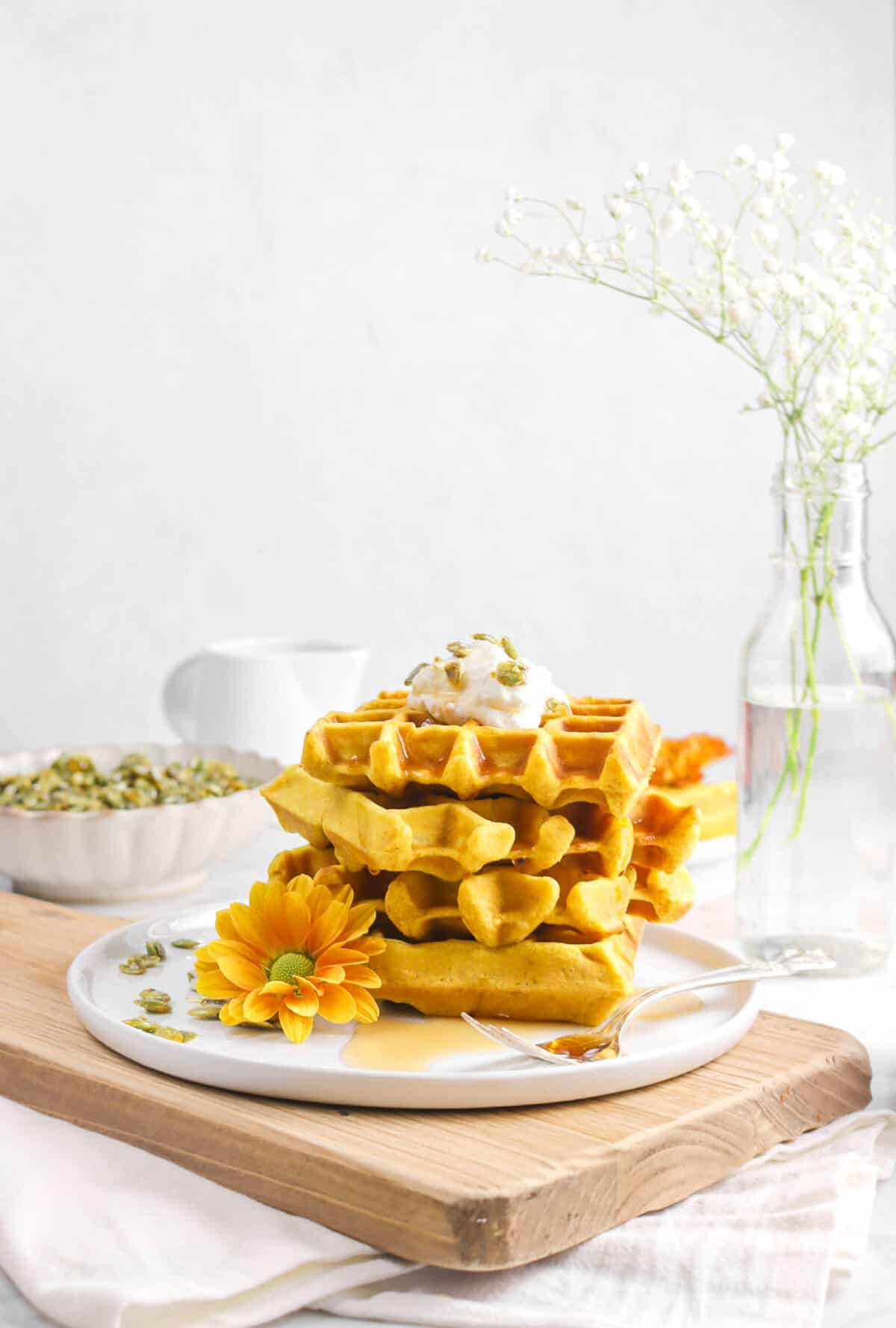 four pumpkin waffled stacked with flowers, whipped cream, and pepitas