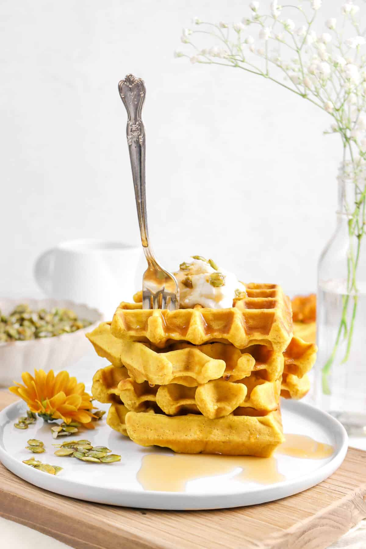 four stacked waffles with a fork in them, maple syrup, flowers, and candied pepitas on wood serving board