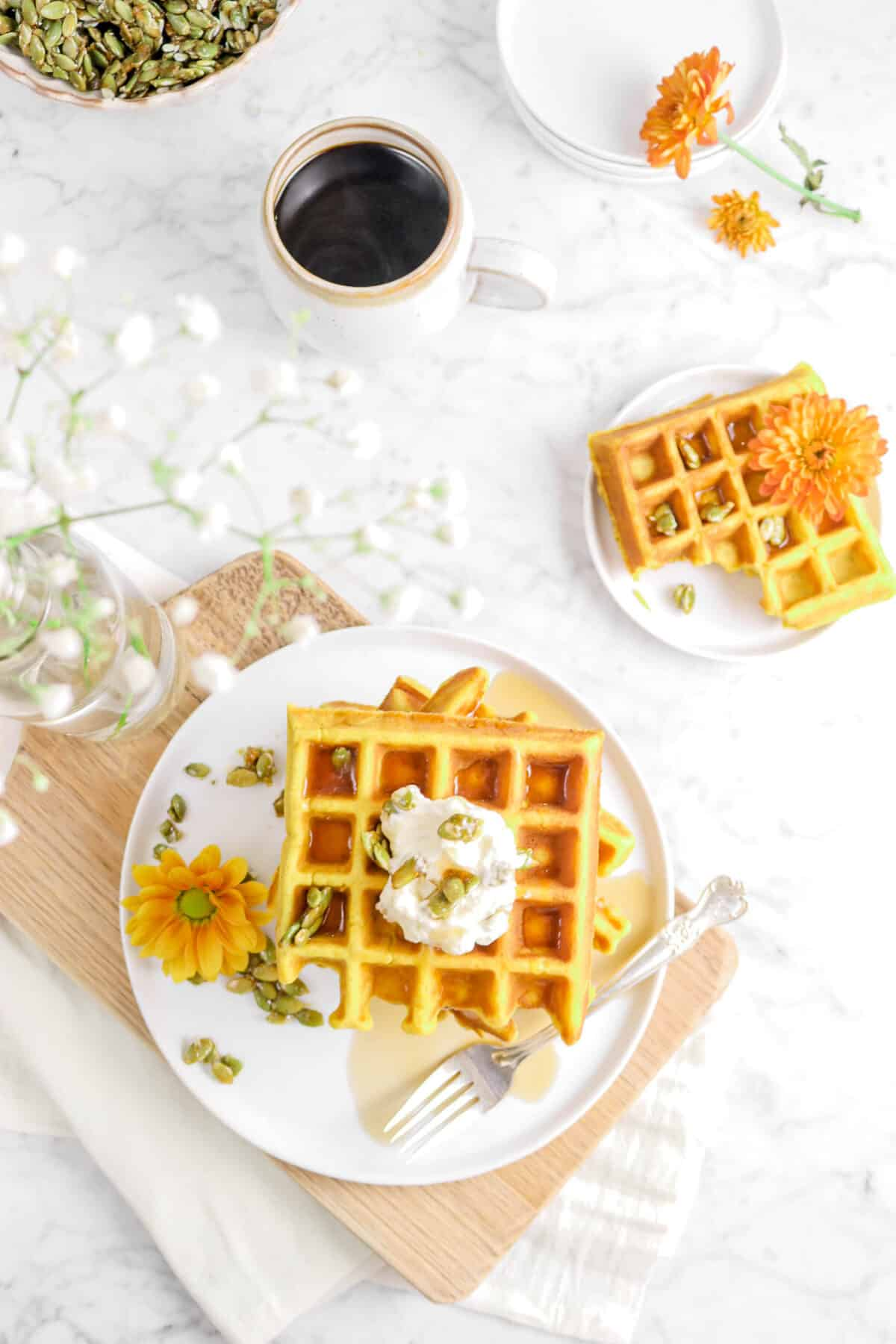 waffles on a white plate with flowers, on a wood serving board, waffle on small white plate, and cup of coffee