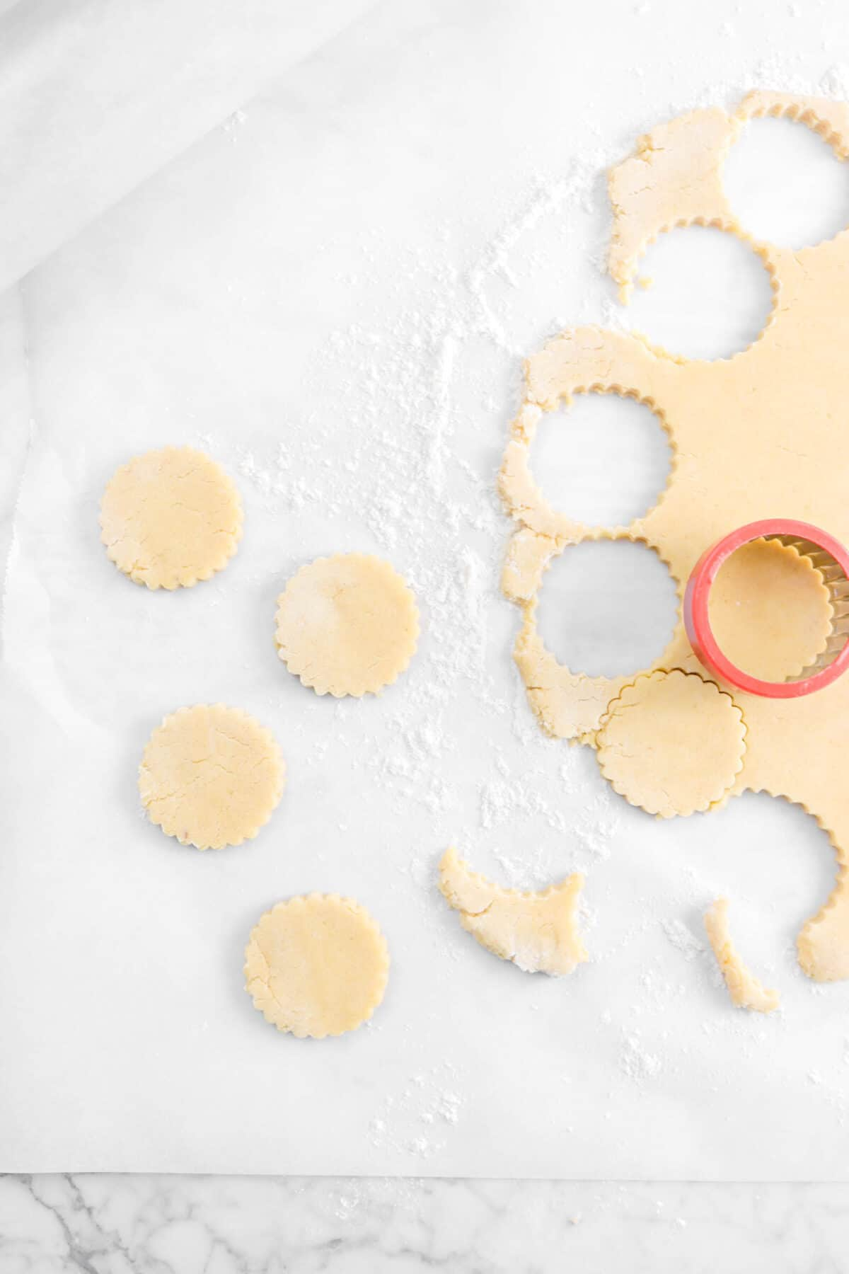 five cookies cut out of dough with cookie cutter on parchment