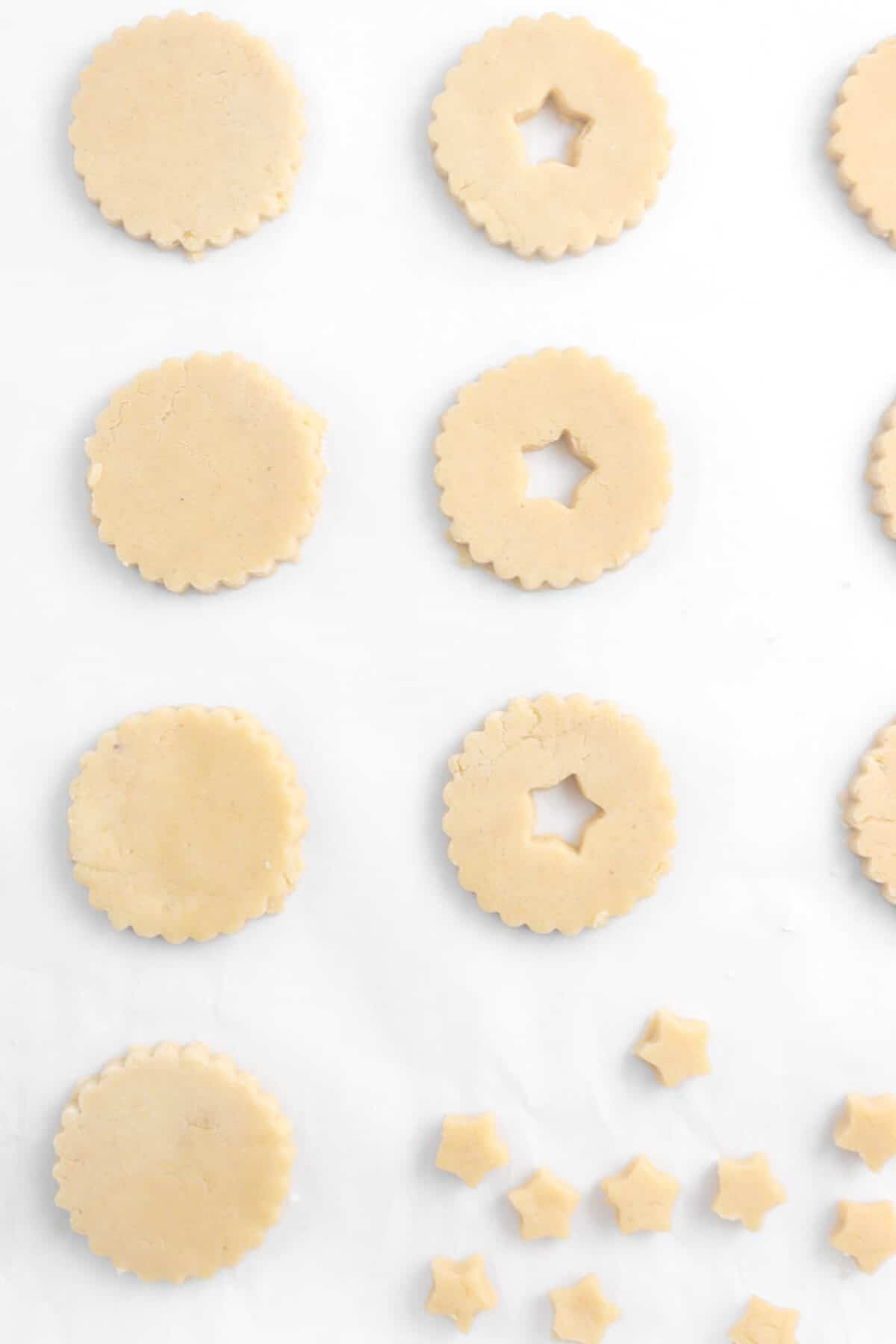 seven cookies on parchment paper with three stars cut out of three cookies