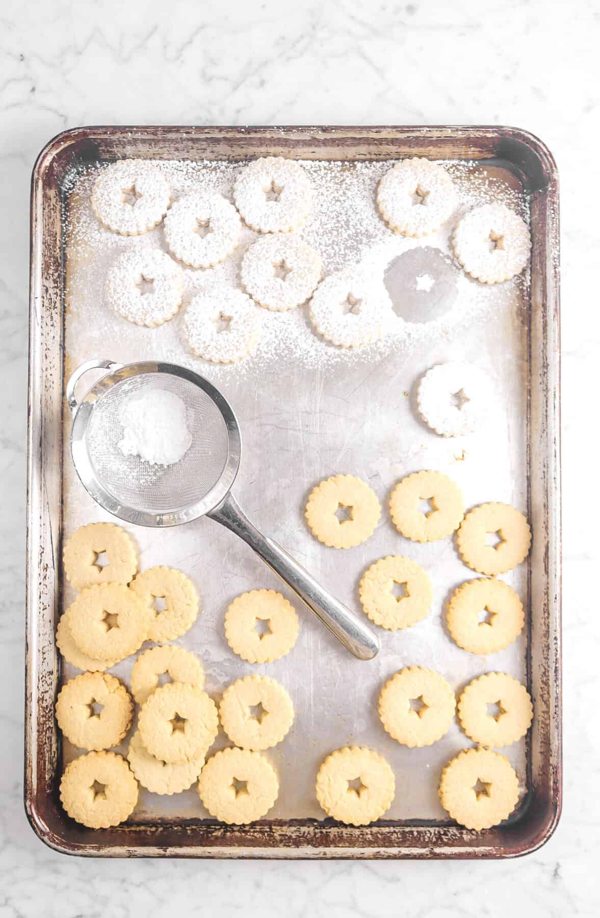 cookies with sieve and powdered sugar dusted on half