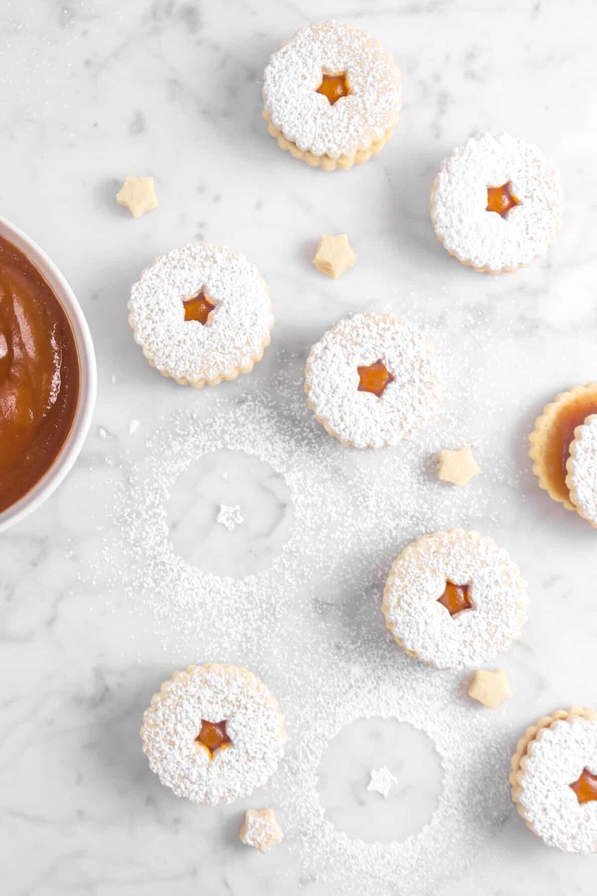 overhead shot of seven apple linzer cookies on marble counter