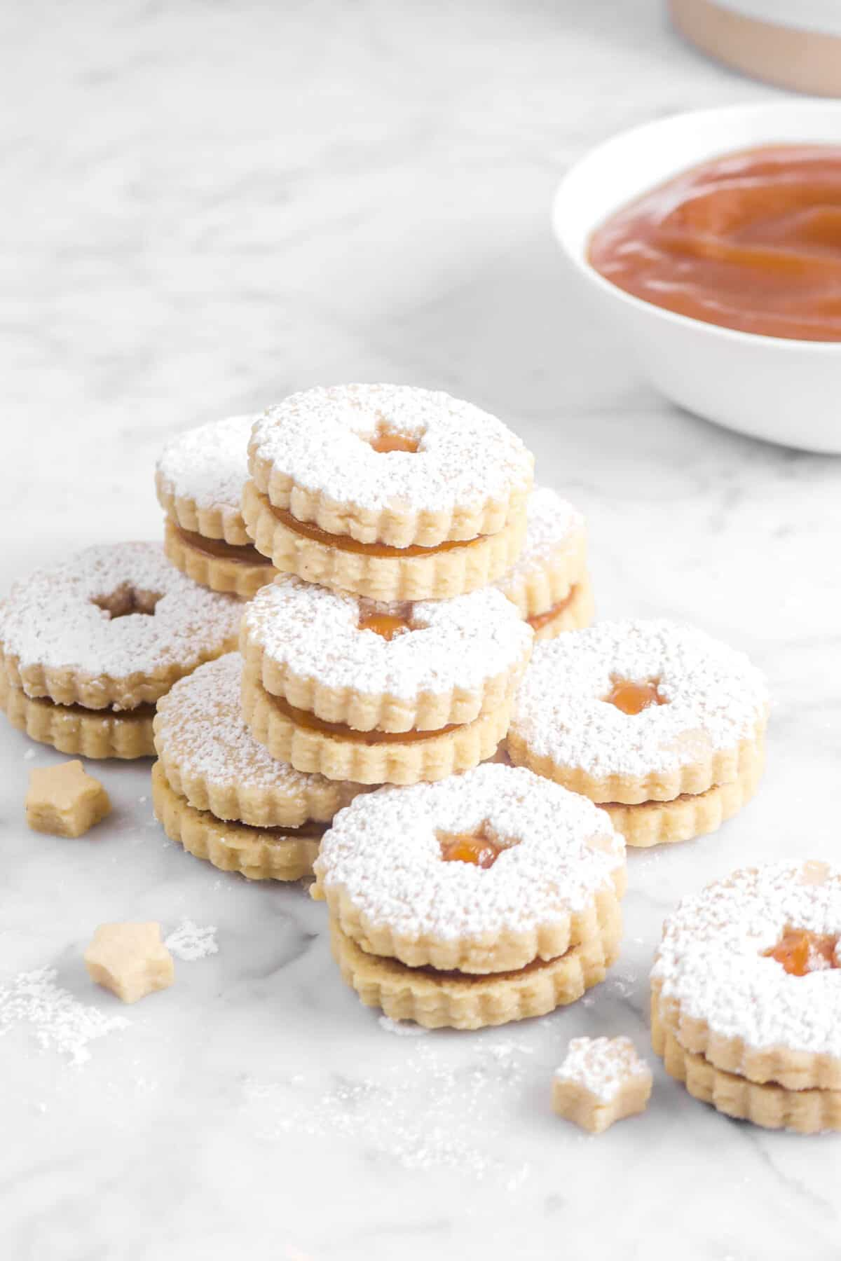 nine apple linzer cookies stacked with three star cookies and a bowl of apple butter