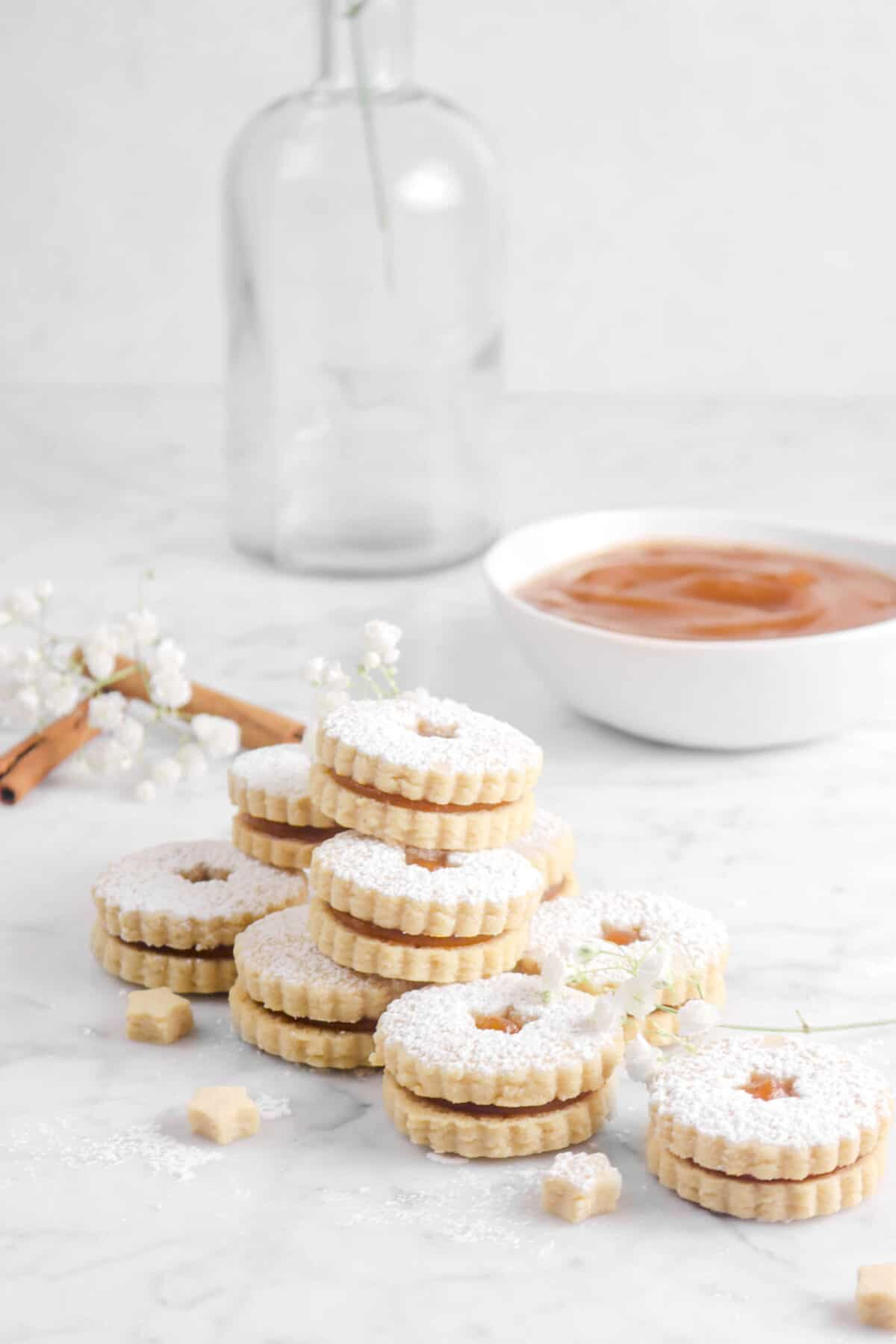 nine apple linzer cookies stacked with flowers, two cinnamon sticks, and a bowl of apple butter