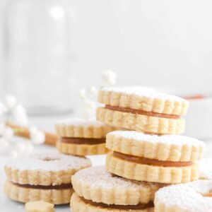 apple butter linzer cookies stacked with white flowers