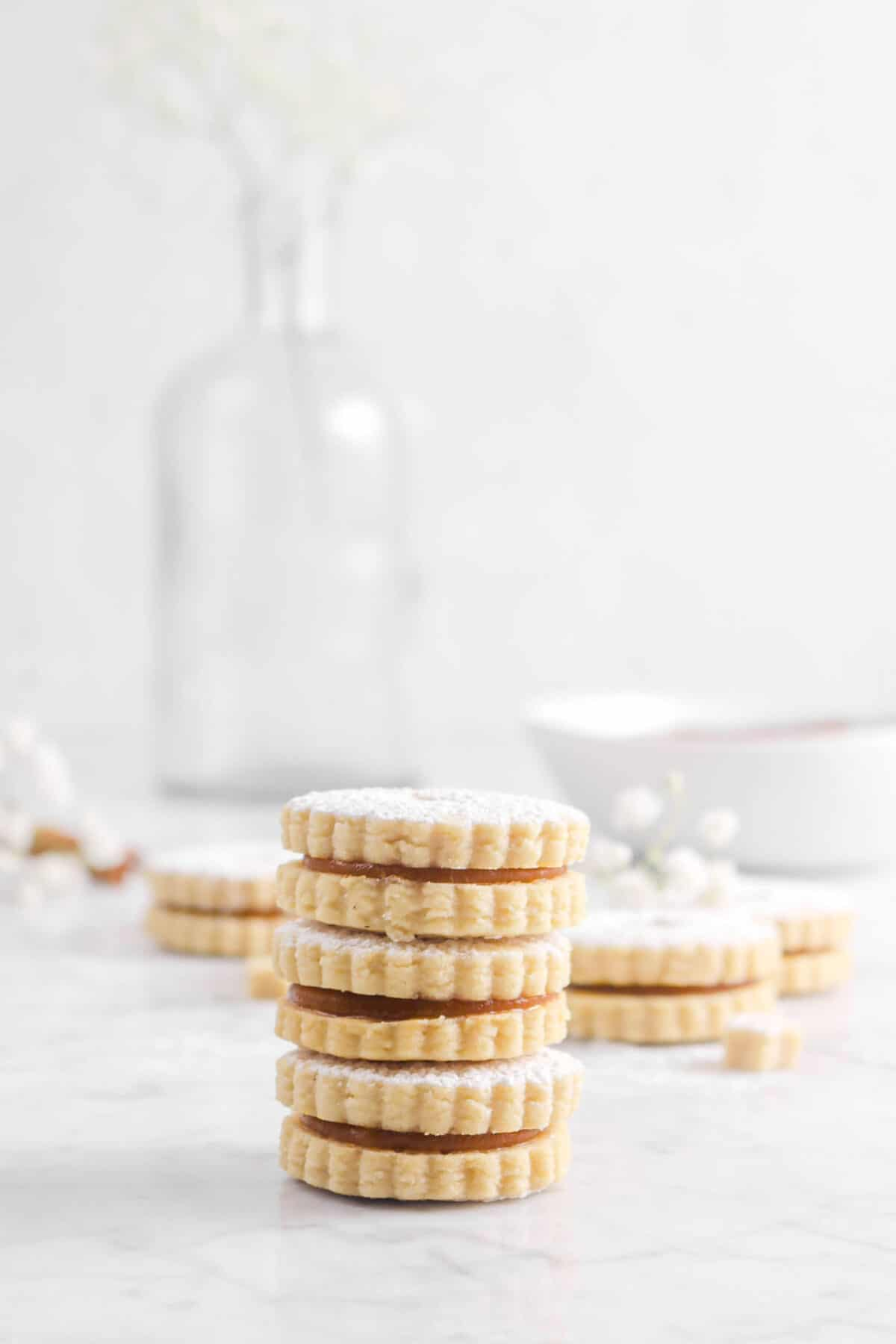 three stacked apple linzer cookies with more cookies behind
