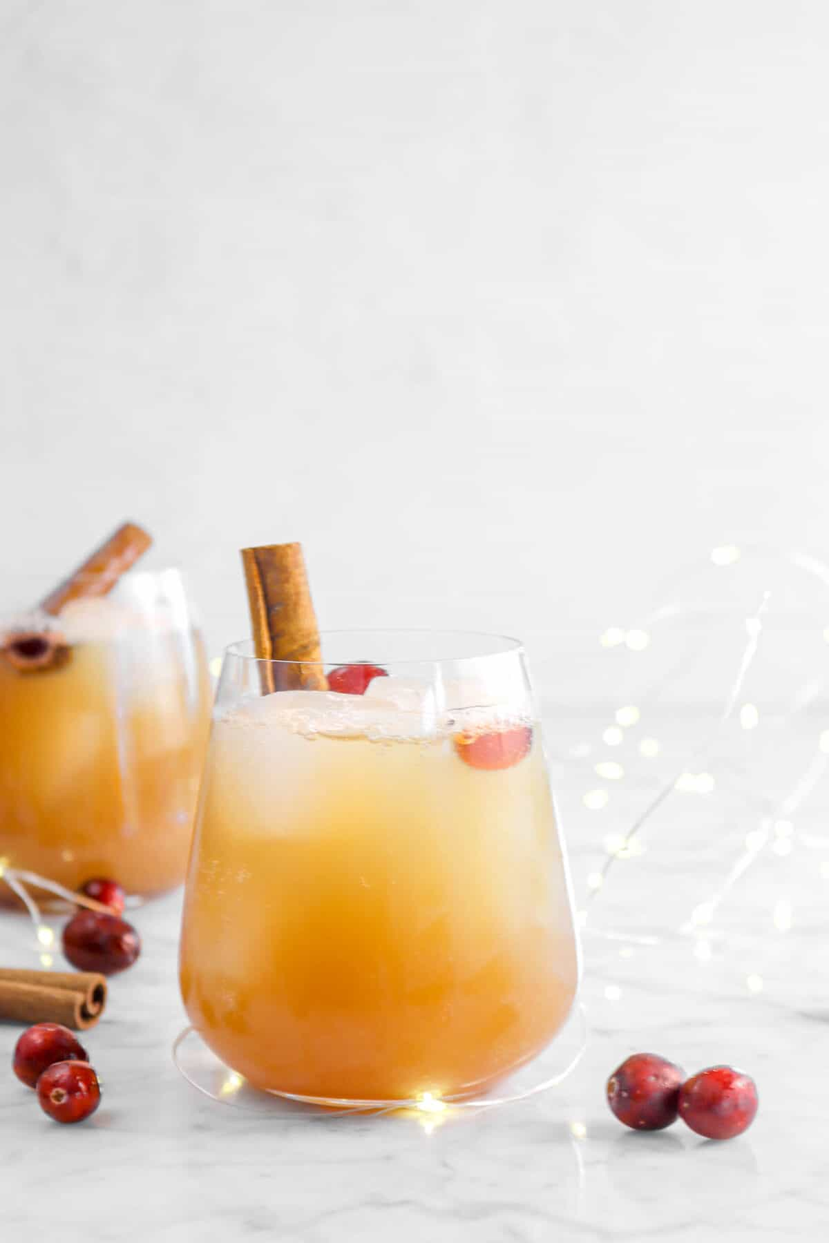 two glasses of cider with cinnamon stick and cranberries