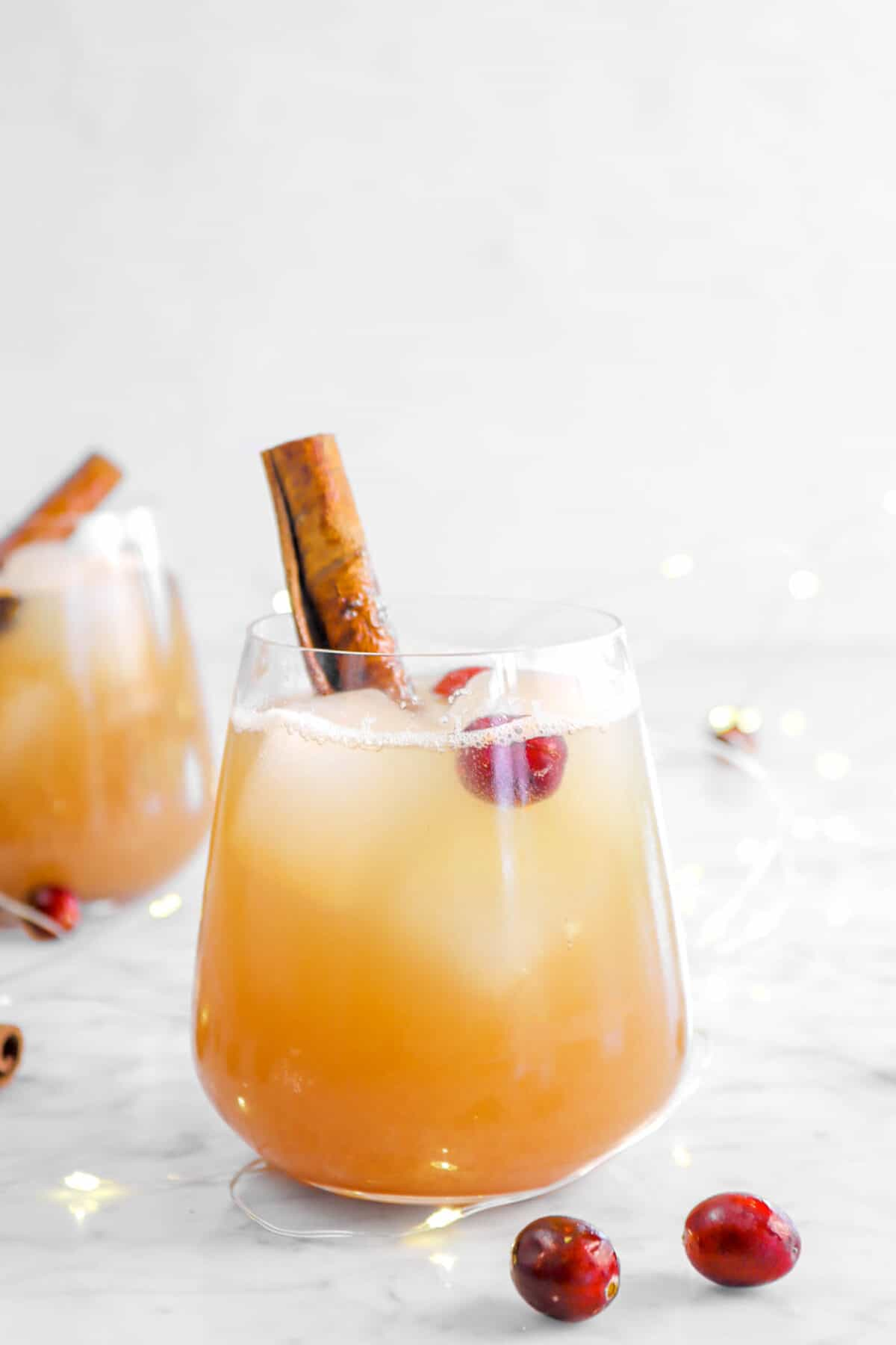 apple cider bourbon fizz in glass with cranberries and cinnamon stick
