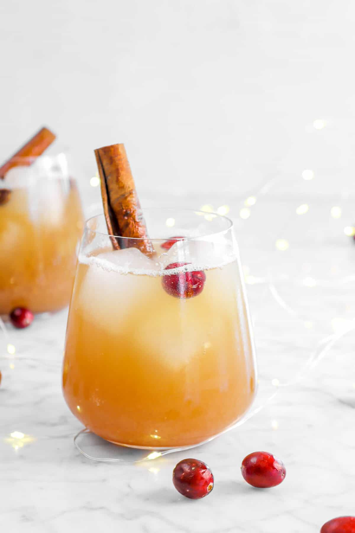 apple fizz in two glasses with cranberries and cinnamon sticks