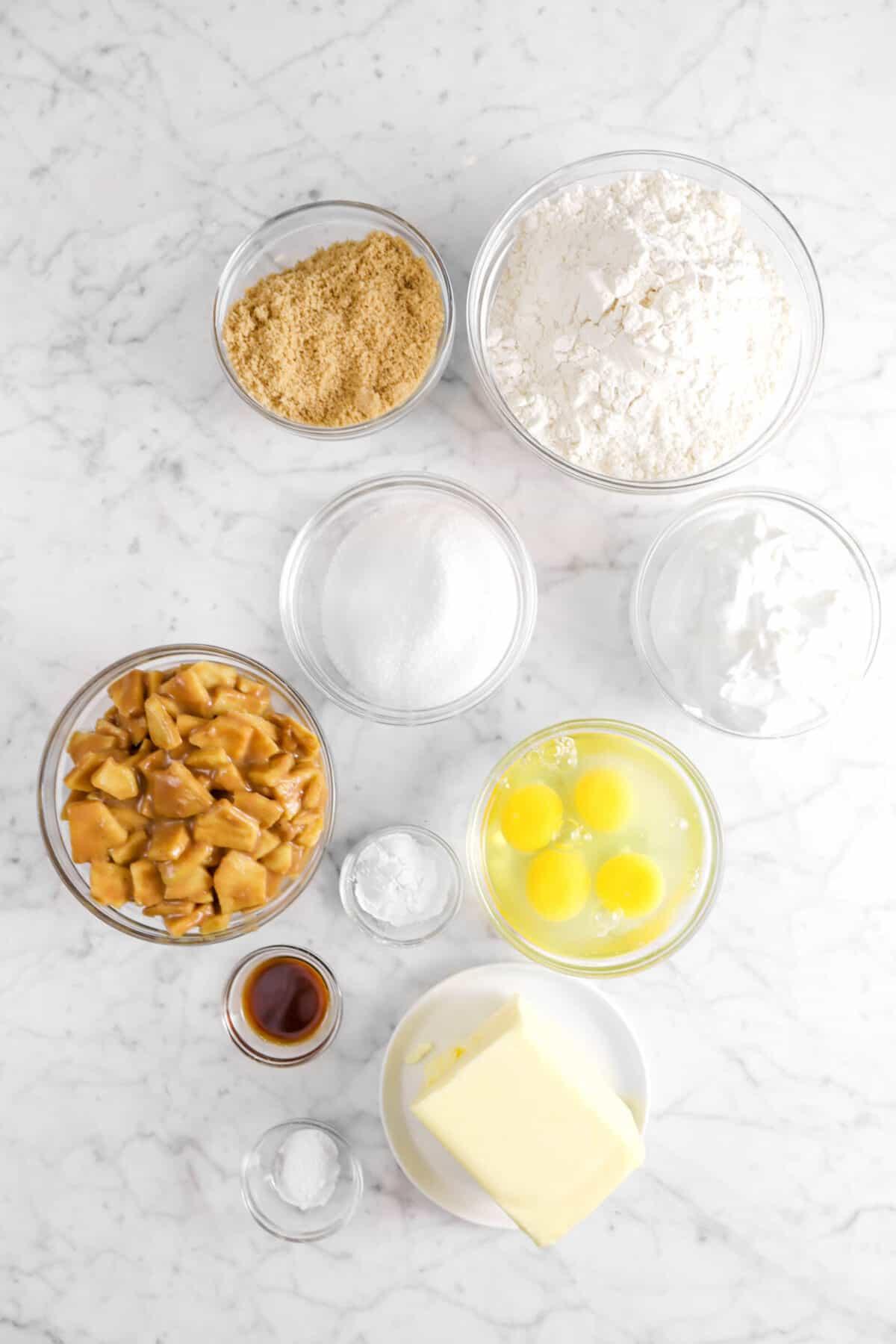 brown sugar, flour, sugar, sour cream, apple pie filling, eggs, baking powder, vanilla, butter, and baking soda in glass bowls