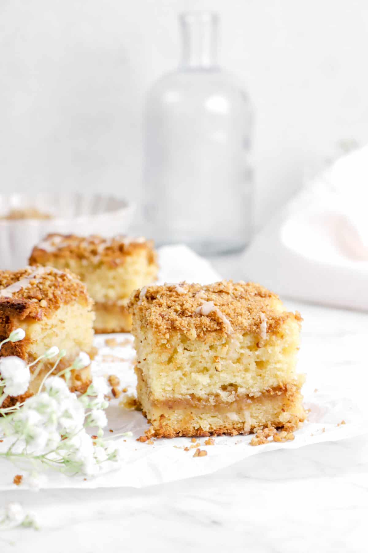 slice of apple pie coffee cake on parchment with flowers