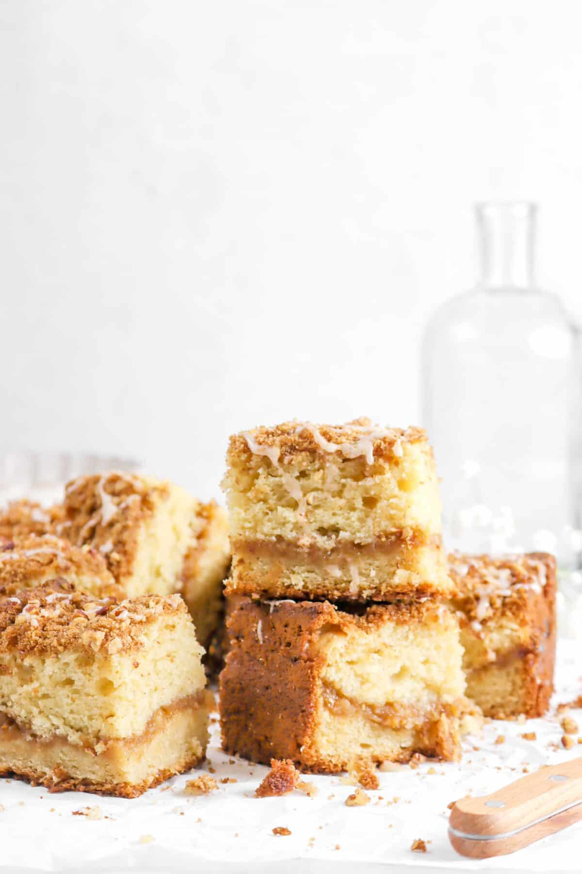 coffee cake slices on parchment paper with glass jar behind