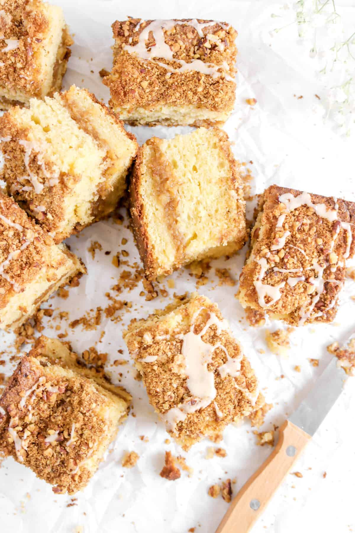 overhead shot of eight slices of coffee cake on parchment paper and a knife
