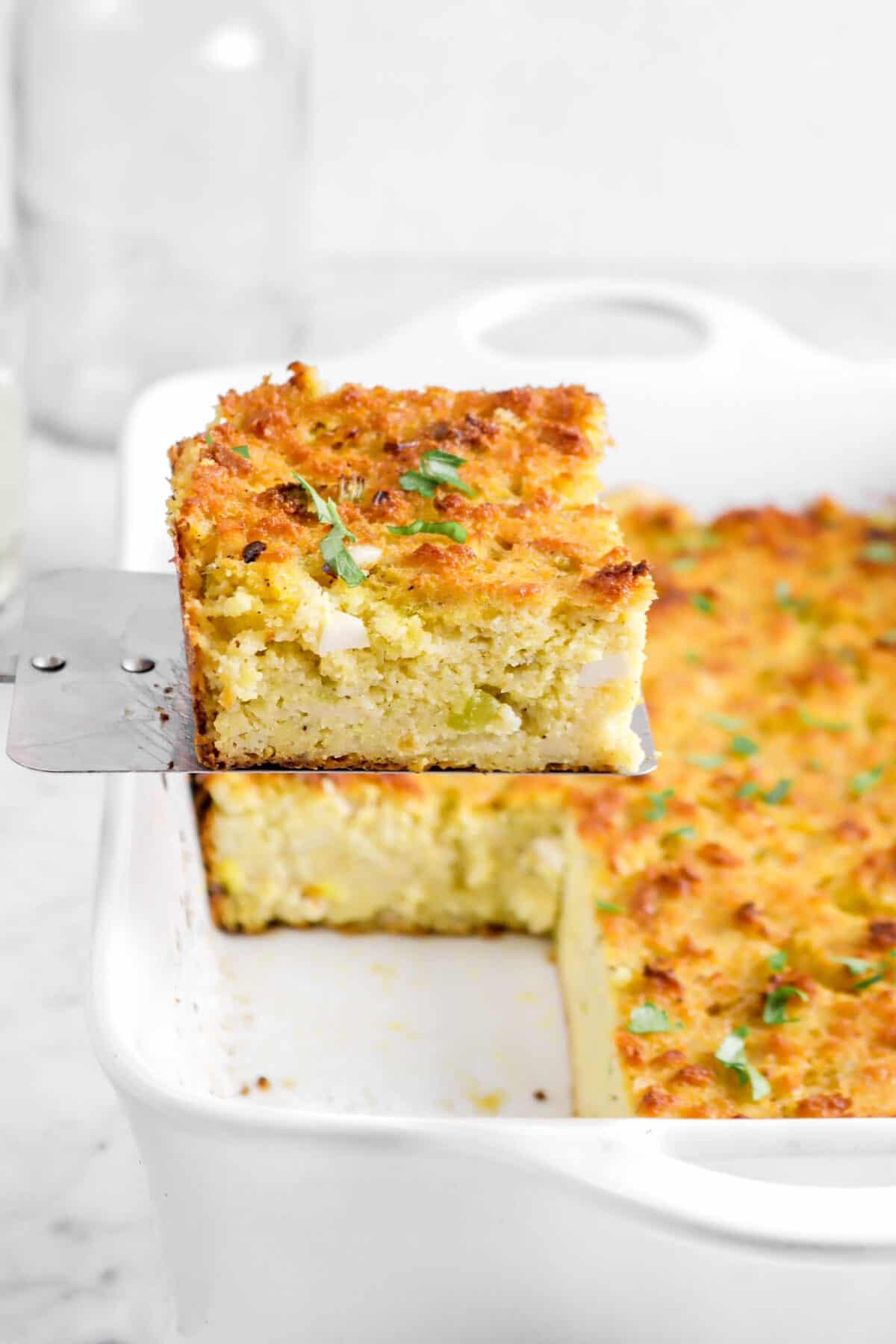 close up of cornbread dressing slice held over casserole