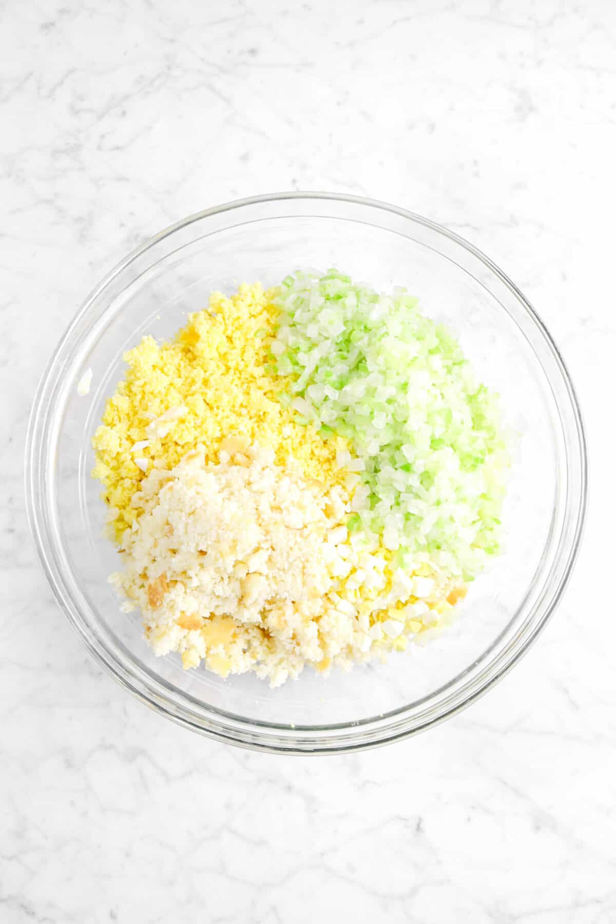cornbread crumbles, chopped egg, biscuit crumbles, and sautéed vegetables in glass bowl