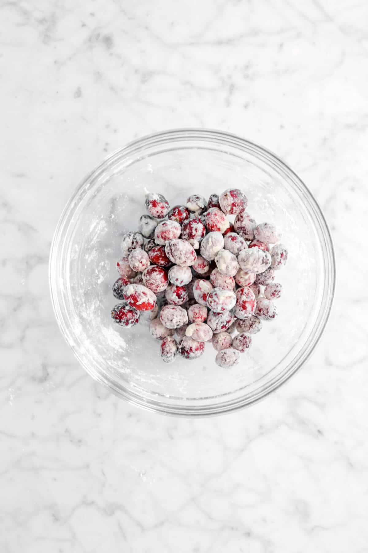cranberries coated in flour in a glass bowl