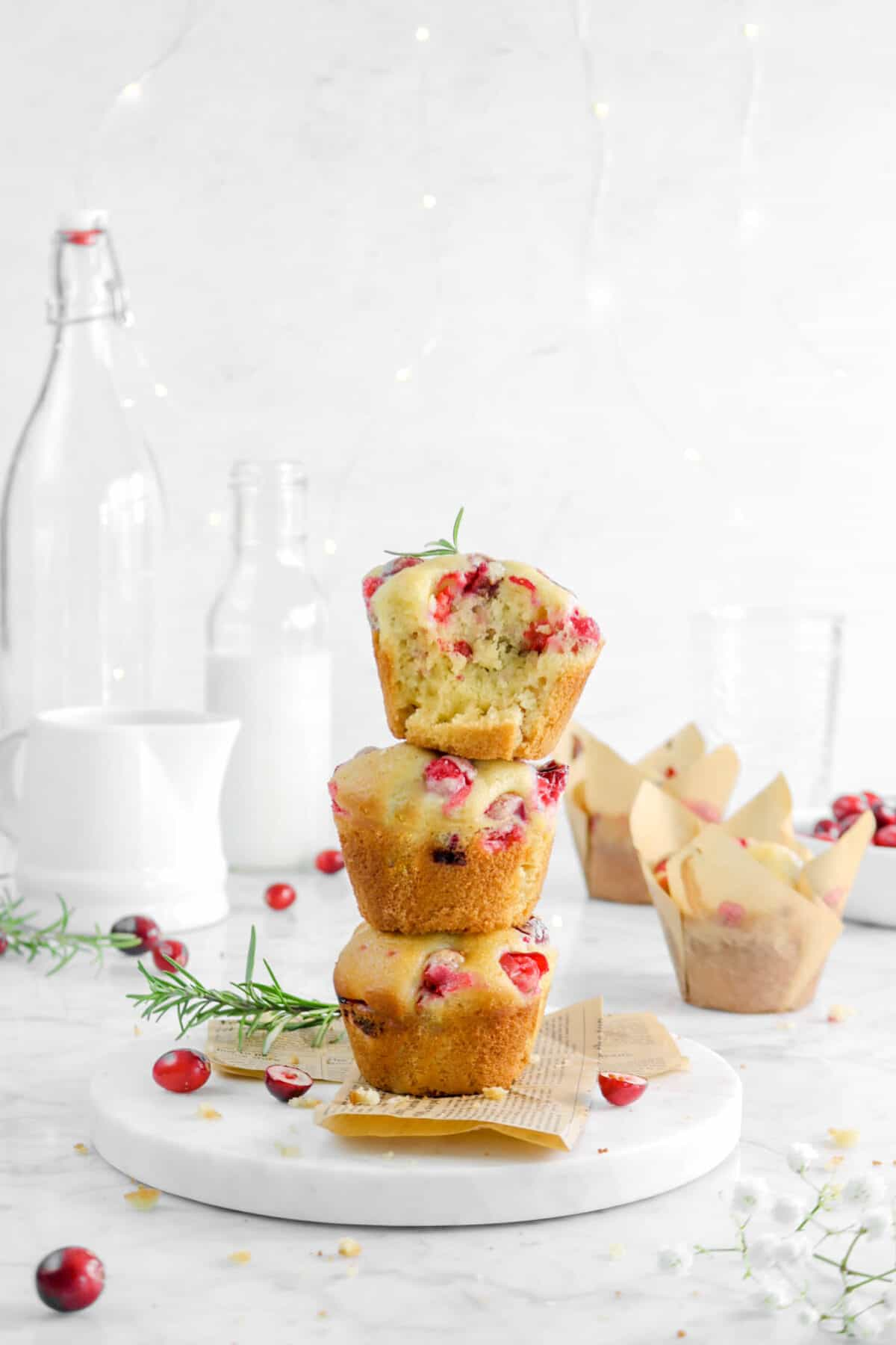 three muffins stacked on marble board with rosemary sprigs, cranberries, milk glasses, and more muffins behind