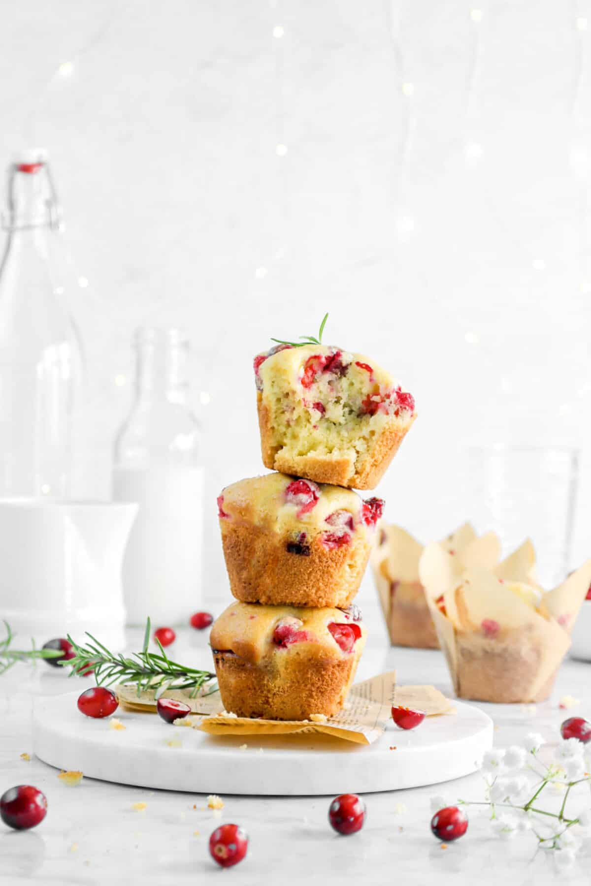 three muffins stackes on white board with cranberries and fairy lights behind