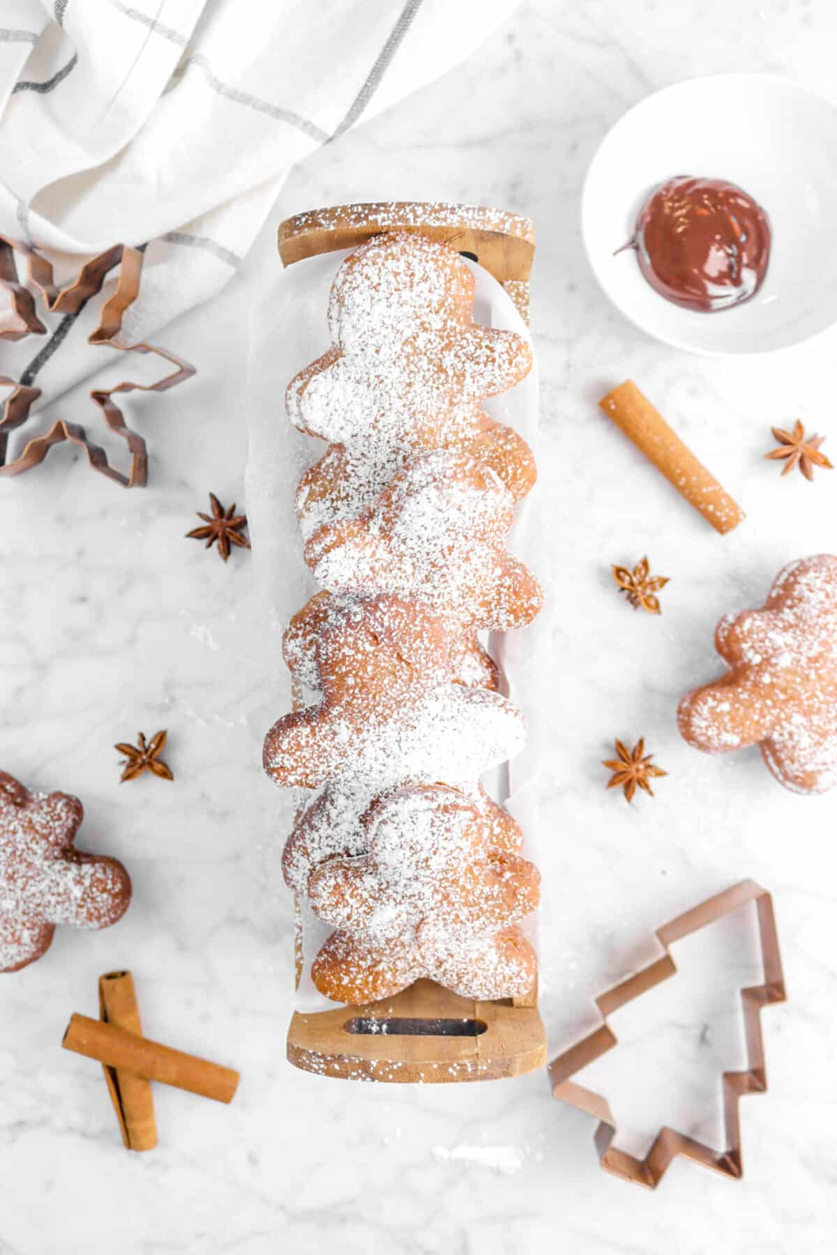 four beignets in wood basket with star anise, cinnamon sticks, copper cutters, two more beignets, and napkin on counter
