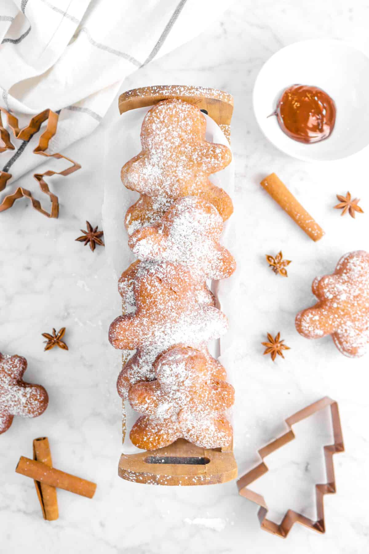 four beignets in wood basket with whole spices and cookie cutters on marble counter