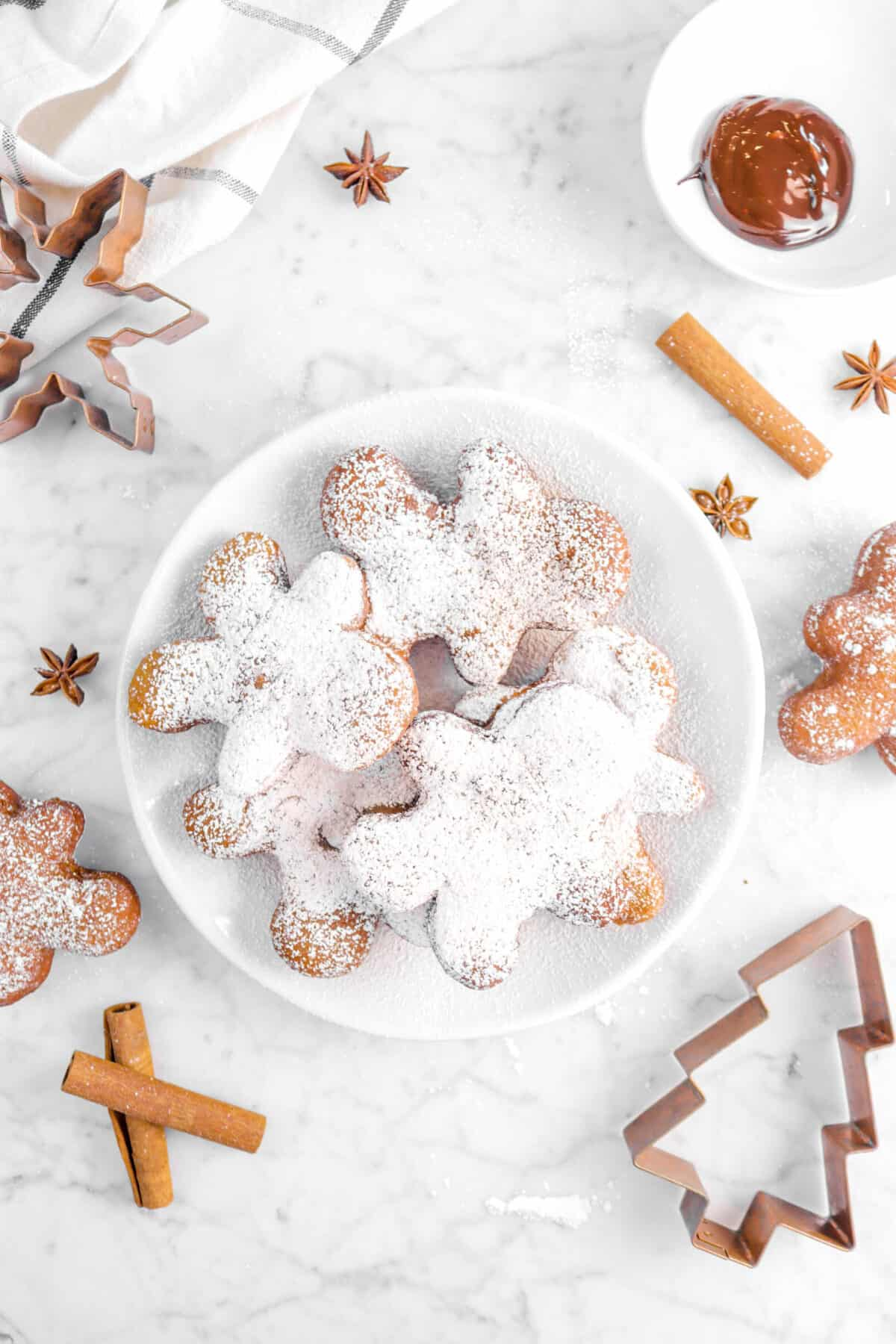 bowl of dusted beignets with whole spices, cookie cutters, chocolate sauce, and more beignets on counter