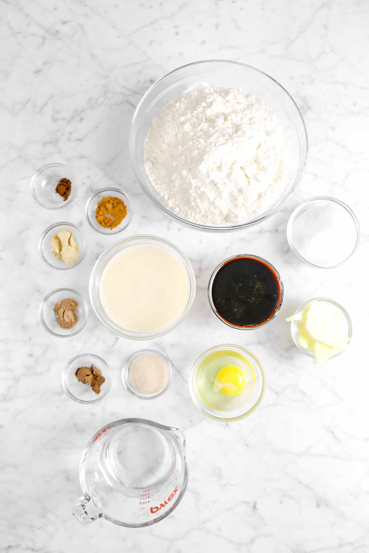 flour, spices, evaporated milk, sugar, molasses, butter, yeast, egg, and water on marble counter