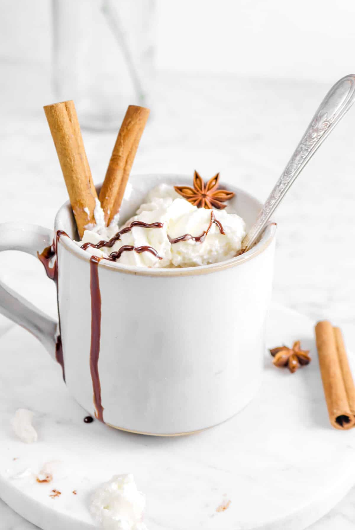 mug with spoon inside, whipped cream , chocolate sauce, and whole spices