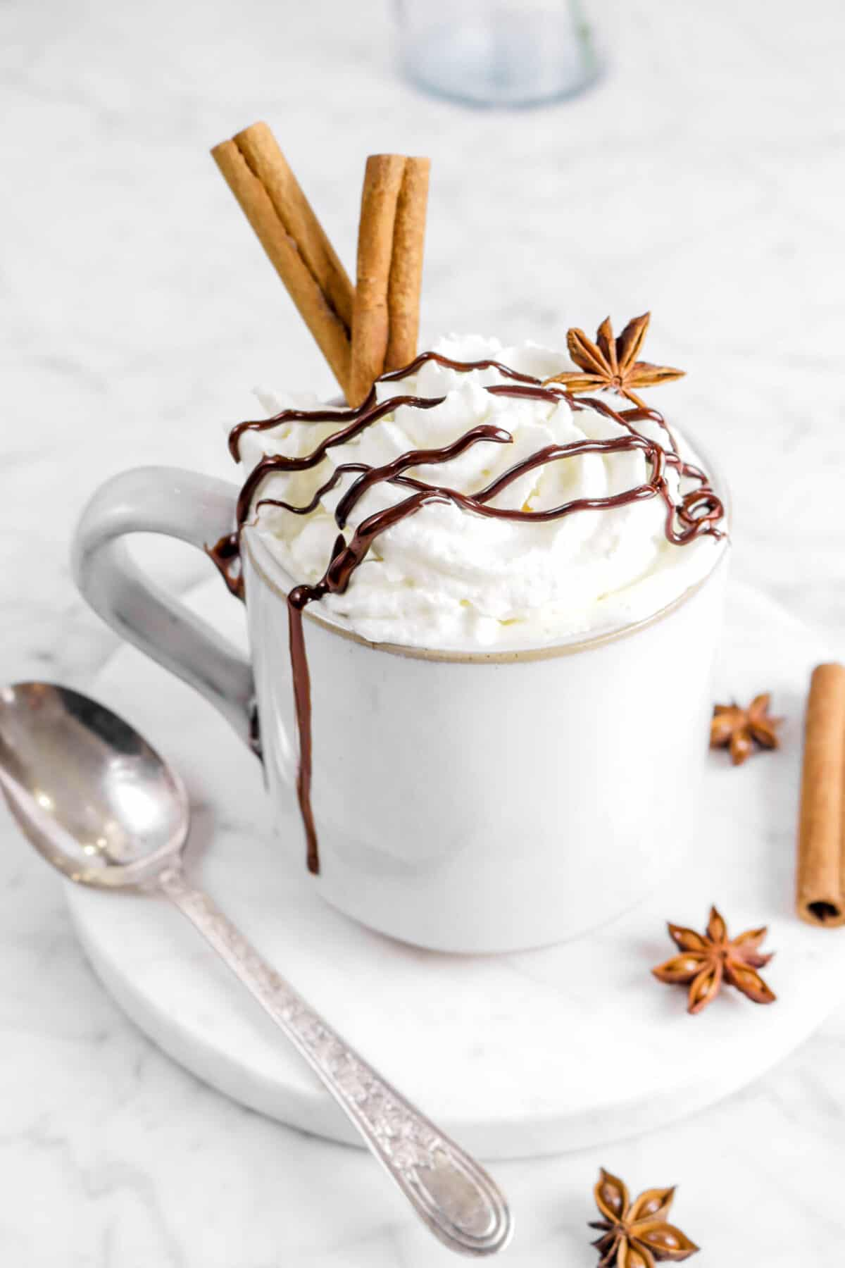 gingerbread mug cake on marble plate with spoon, cinnamon sticks, and star anise